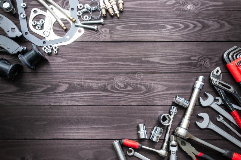 Hulpmiddelen en autovervangstukken op houten werkbank De ruimte van het exemplaar stock fotografie