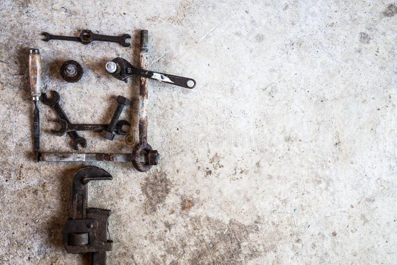 Hulpmiddelen en delen in de vorm van een smileygezicht worden geschikt op cement dat stock foto