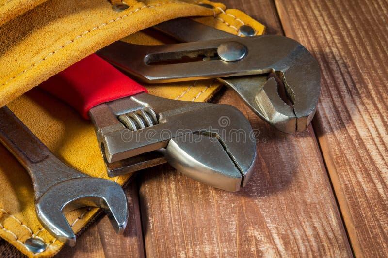 Hulpmiddelen en instrumenten in leerzak die op houten achtergrond wordt geïsoleerd royalty-vrije stock foto