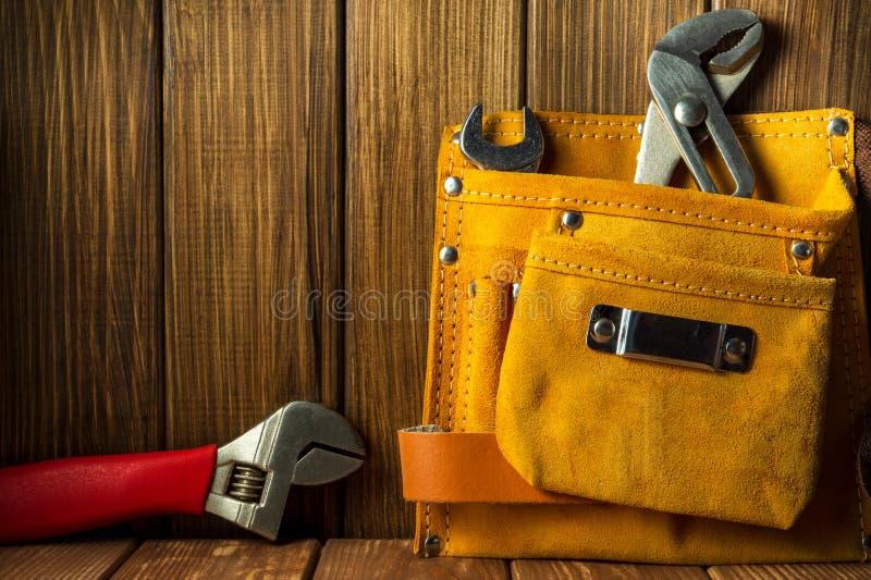 Hulpmiddelen en instrumenten in leerzak op houten achtergrond stock foto