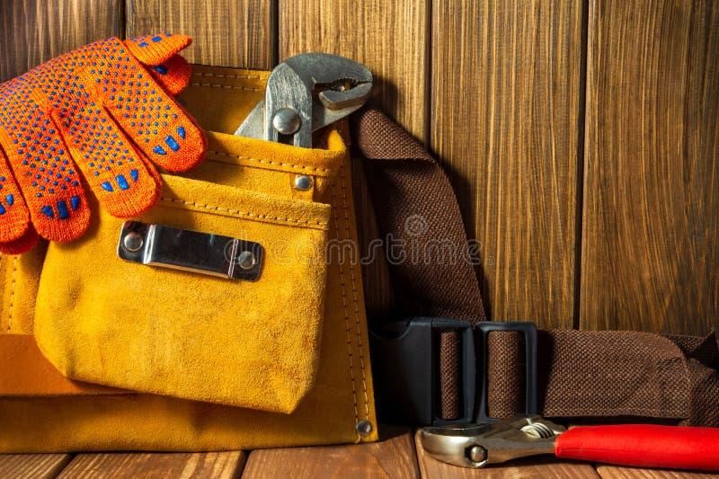 Hulpmiddelen en instrumenten in leerzak op houten achtergrond stock afbeelding