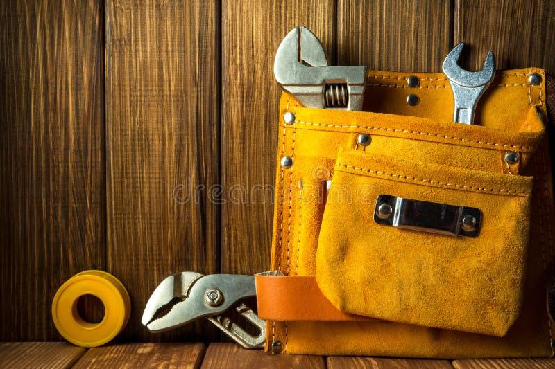 Hulpmiddelen en instrumenten in leerzak op houten achtergrond royalty-vrije stock foto