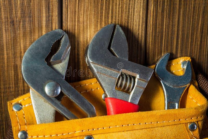 Hulpmiddelen en instrumenten in leerzak op houten achtergrond stock foto's