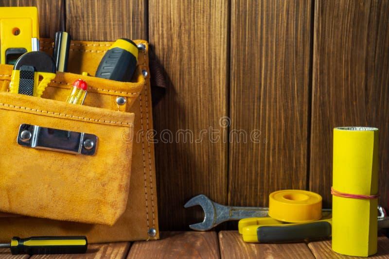 Hulpmiddelen en instrumenten in leerzak op houten achtergrond royalty-vrije stock afbeeldingen