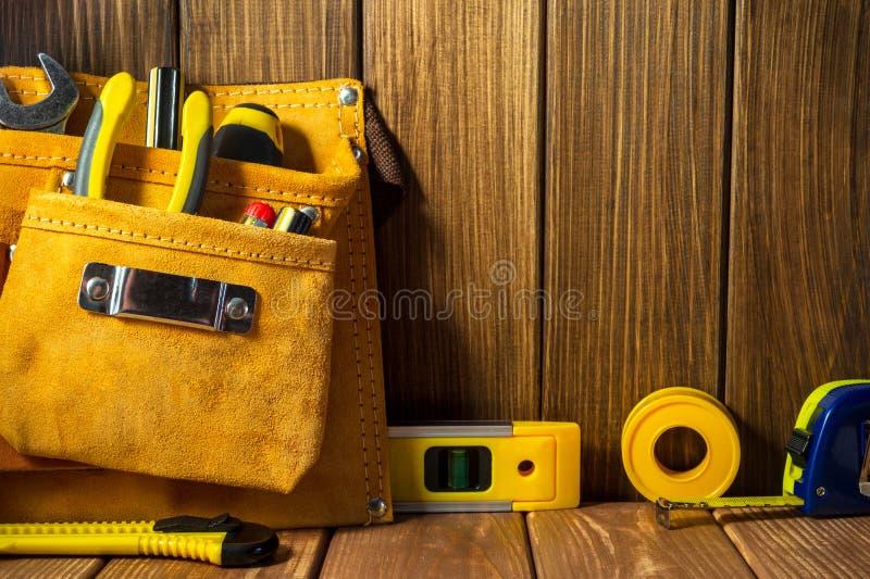 Hulpmiddelen en instrumenten in leerzak op houten achtergrond stock fotografie