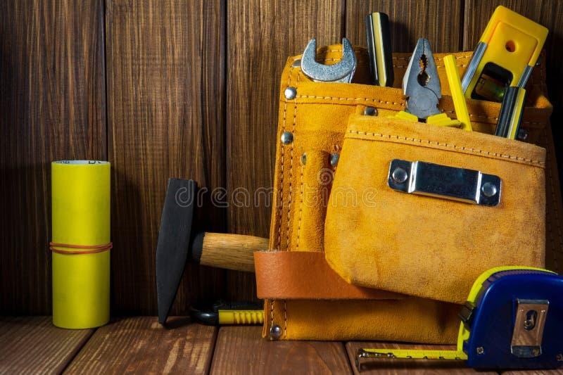 Hulpmiddelen en instrumenten in leerzak op houten achtergrond wordt geïsoleerd die royalty-vrije stock foto
