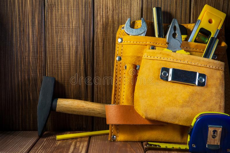 Hulpmiddelen en instrumenten in leerzak op houten achtergrond wordt geïsoleerd die royalty-vrije stock afbeelding