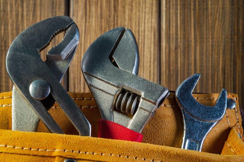 Hulpmiddelen en instrumenten in leerzak op houten achtergrond wordt geïsoleerd die stock foto