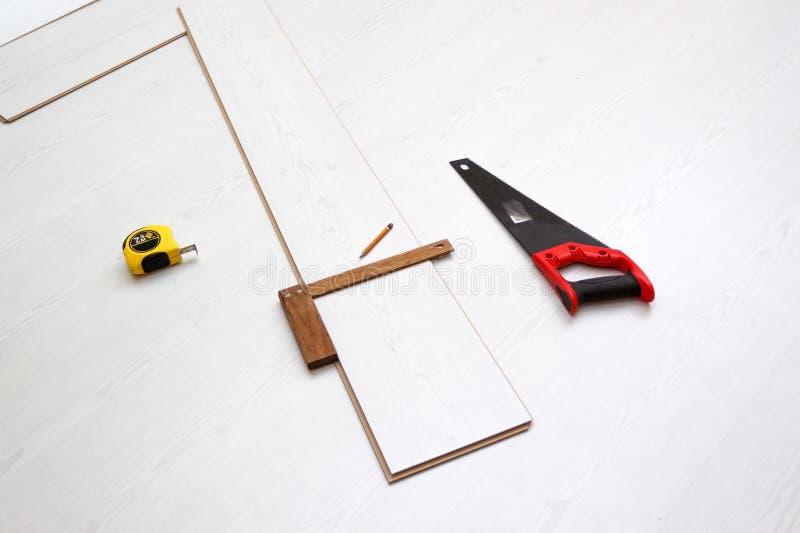 Hulpmiddelen om gelamineerde vloerraad, concept het huisverbeteringen proces te snijden stock afbeelding