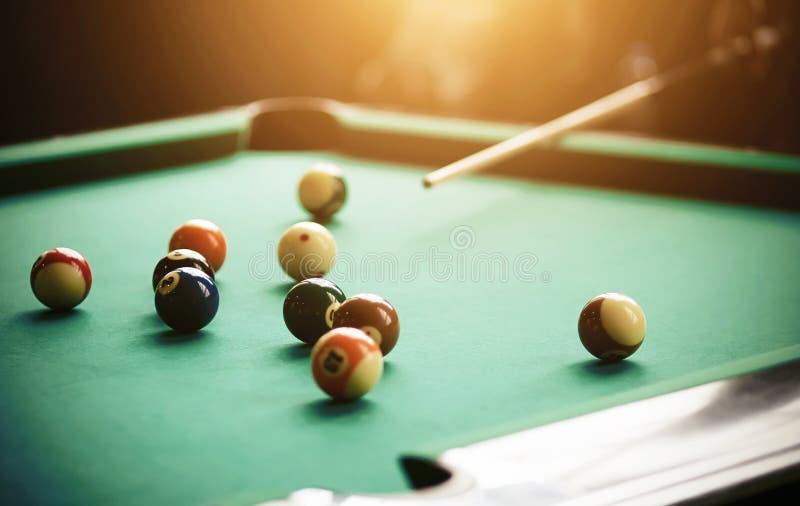 A human aims a cue at billiard balls stock image