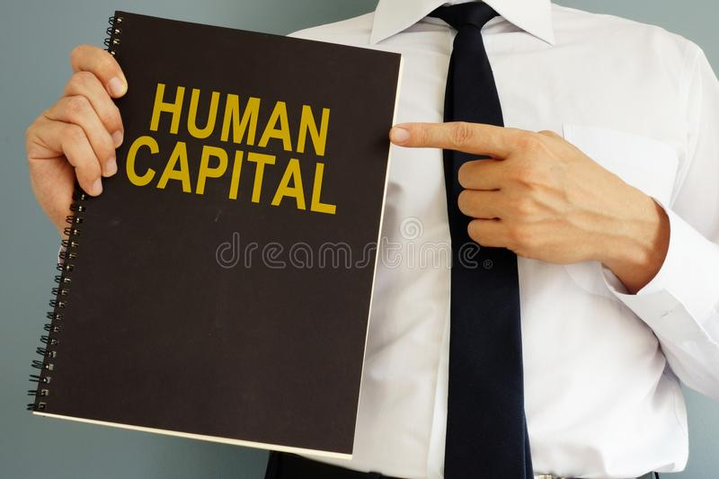 Human Capital concept. Manager holding book. royalty free stock photo