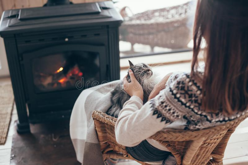 Human with cat relaxing by the fire place. Human with cat relaxing in wicker armchair by the fire place in wooden cabin. Warm and cozy winter holiday concept stock image