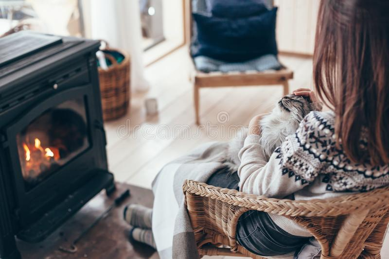 Human with cat relaxing by the fire place. Human with cat relaxing in wicker armchair by the fire place in wooden cabin. Warm and cozy winter holiday concept stock photo