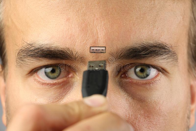 Human connects wire to the connector on his face between eyes, closeup, concept stock images