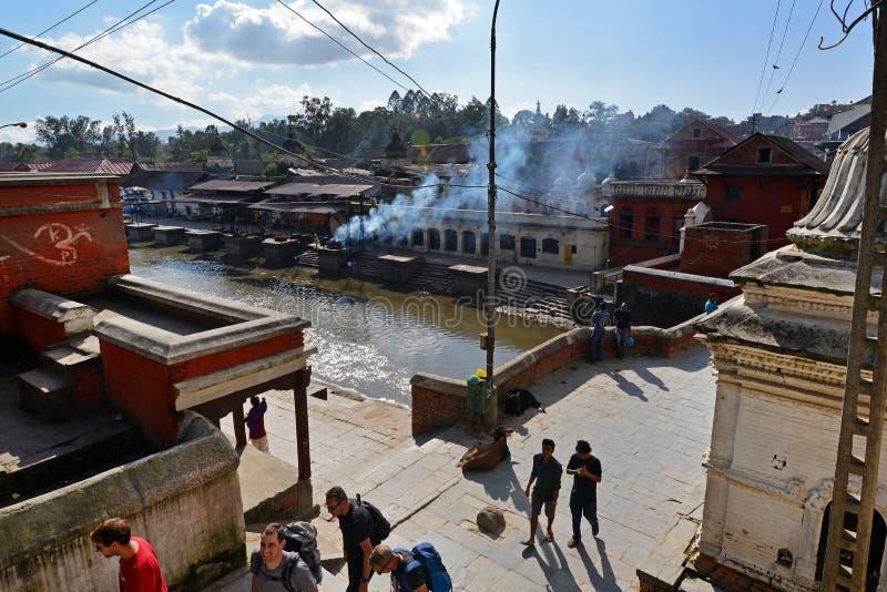 Human cremation ghtas along the holy Bagmati river. Pashupatinath, Nepal. PASHUPATINATH - OCT 8: Cremation ghats and ceremony along the holy Bagmati River at royalty free stock photography