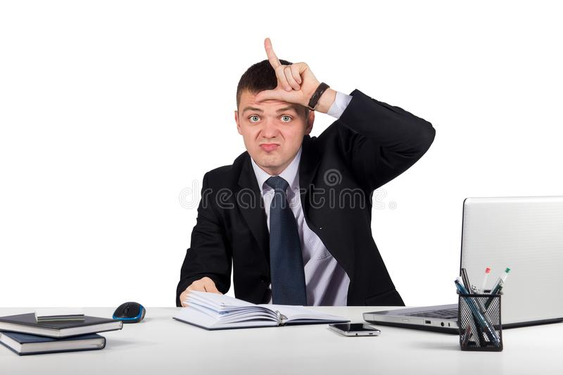 Young businessman showing loser sign on forehead, looking at you isolated on white background stock image