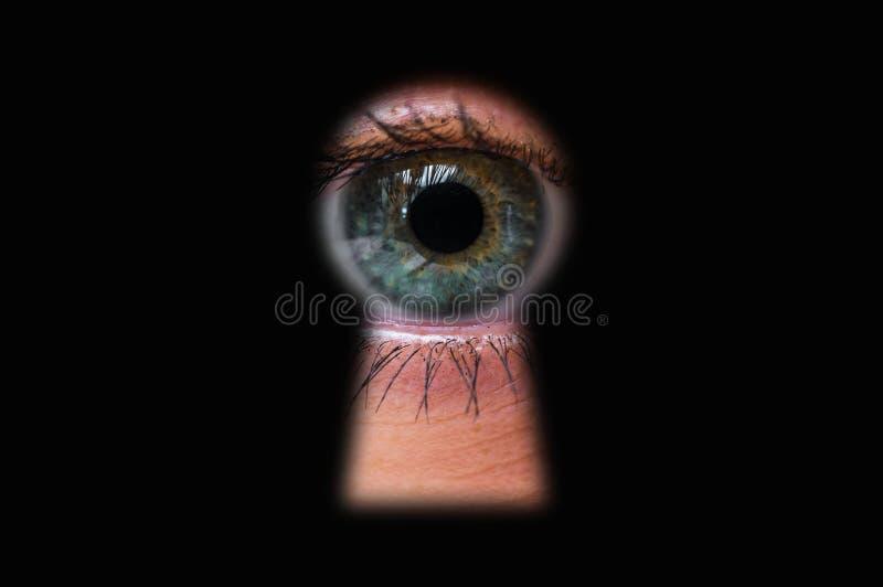 Human eye behind door looking through a keyhole. Voyeurism concept royalty free stock image