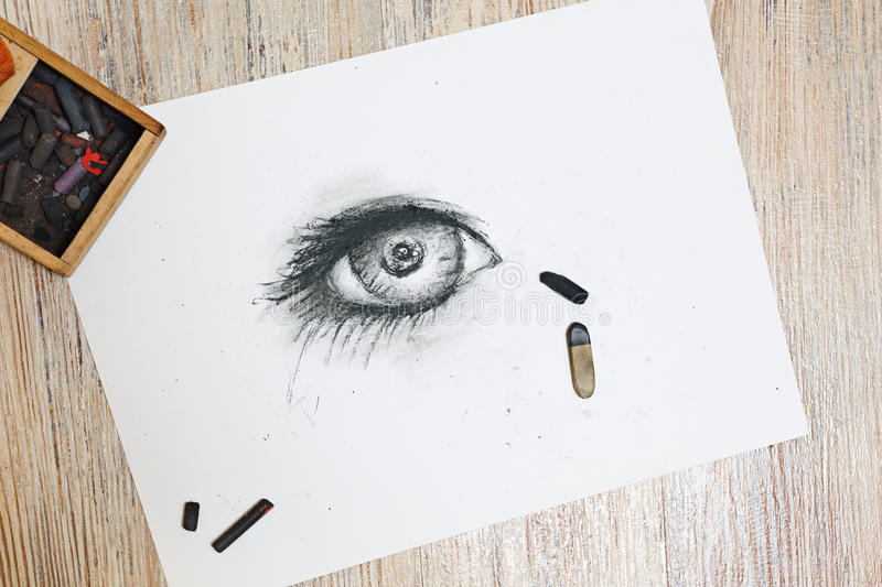 Human eye is drawn in charcoal on paper. stock image
