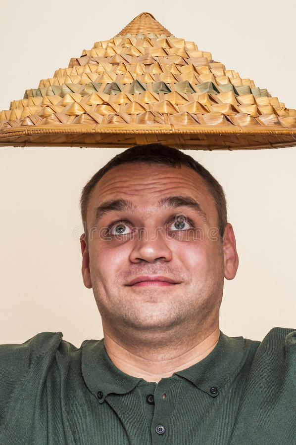 Surprised man looking up on straw hat above his head. stock image