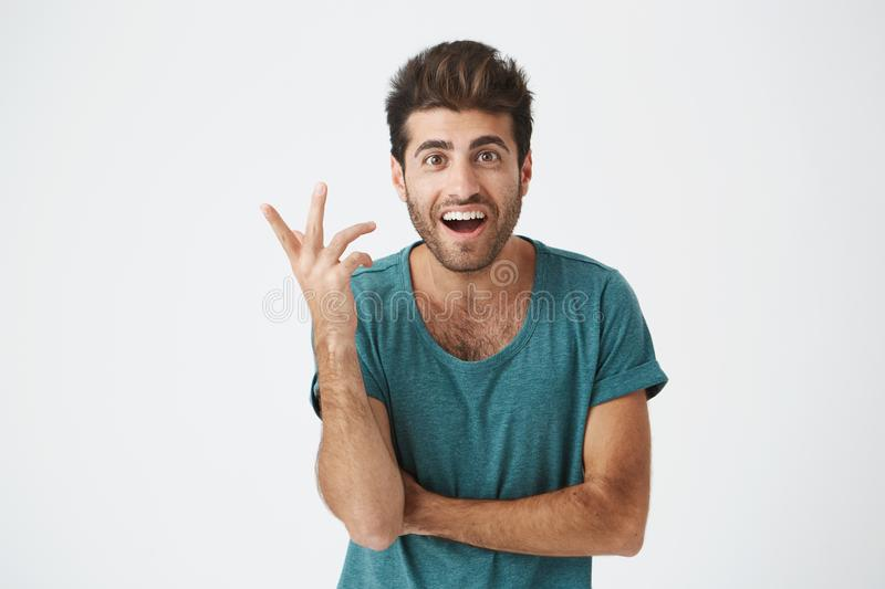 Human face expressions, emotions and feelings. Astonished and surprised bearded young man in blue t-shirt pointing at stock photo