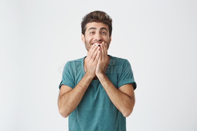 Human face expressions, emotions and feelings. Astonished and surprised bearded young man in blue t-shirt pointing at royalty free stock image