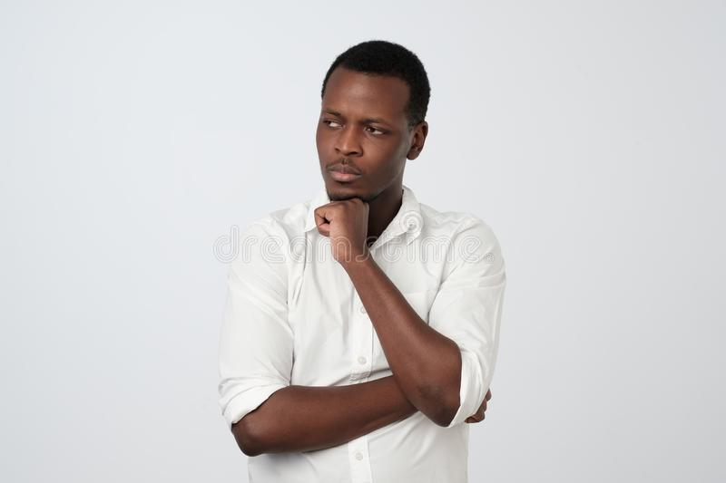 African american man looking aside with thoughtful and skeptical expression, trying to remember something stock photo