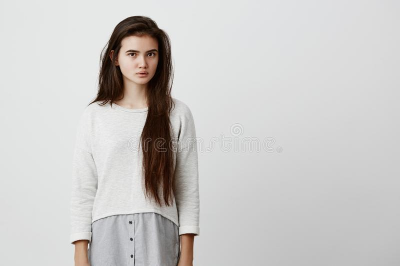 Human face expressions and emotions. Thoughtful young beautiful female with dark long straight hair in casual clothing stock image