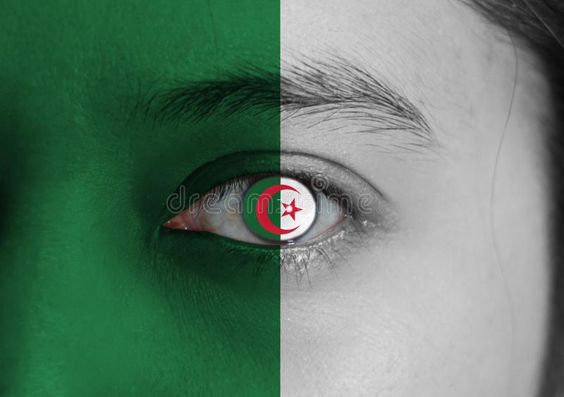 Human face painted Algeria flag with a red star and crescent on the center of eye or eyeball stock image