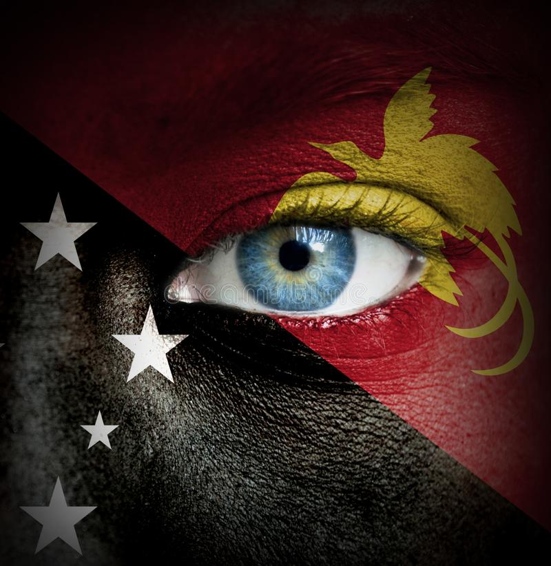 Human face painted with flag of Papua New Guinea royalty free stock photo