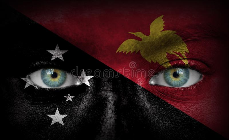 Human face painted with flag of Papua New Guinea stock photography