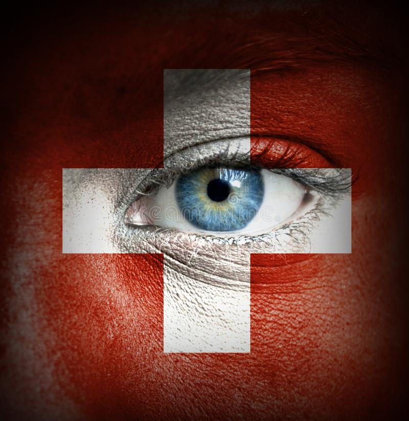 Human face painted with flag of Switzerland stock photography