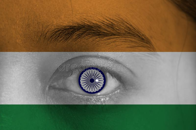 Human face painted with Indian flag and Ashoka Chakra Wheel on the center of eye or eyeball. Human eye painted with flag of India stock image