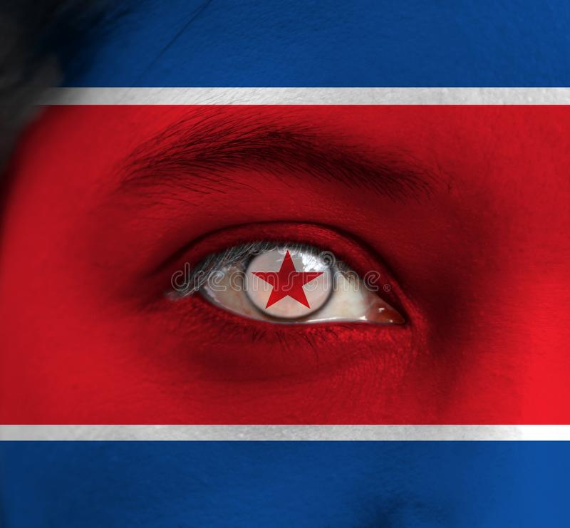 Human face painted North Korea flag with red star within a white circle on the center of eye or eyeball. Human eye painted with flag of Democratic People`s stock image