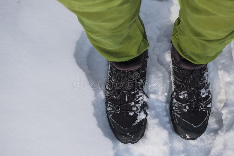 Human feet in hiking boots in the snow. Human feet in hiking boots in the white snow royalty free stock photos