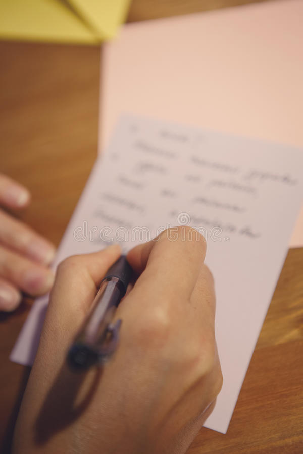 Human female hand holding pen and writing letter or text on paper royalty free stock photos