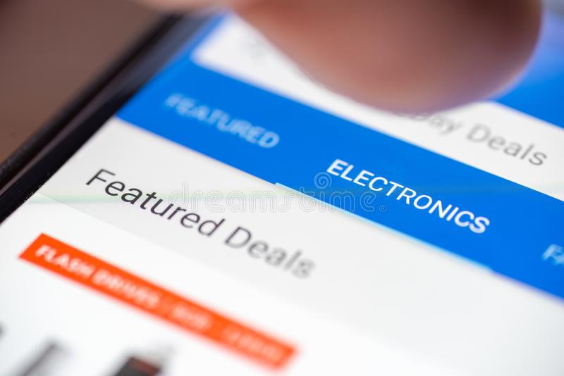 Human finger thumb over Electronics category button link on shopping app on smartphone screen closeup.  royalty free stock image