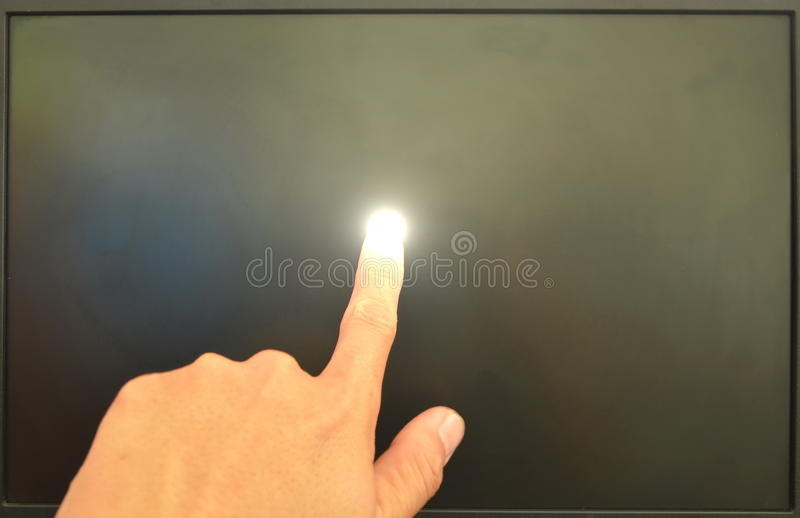 Human finger touching on computer screen and light. Human finger touching on black computer screen and light on stock image