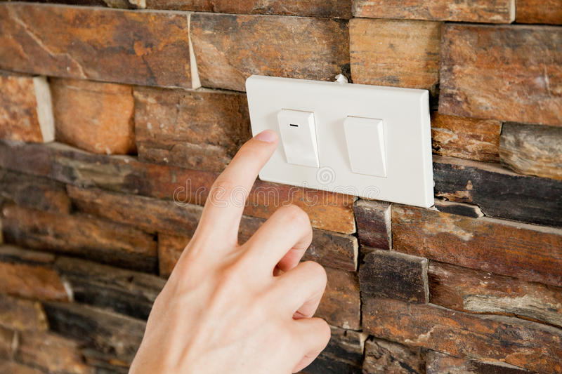 Human finger turning off the light switch - green earth and energy saving concept stock images