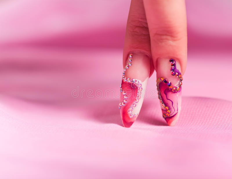 Human fingers with long fingernail over pink