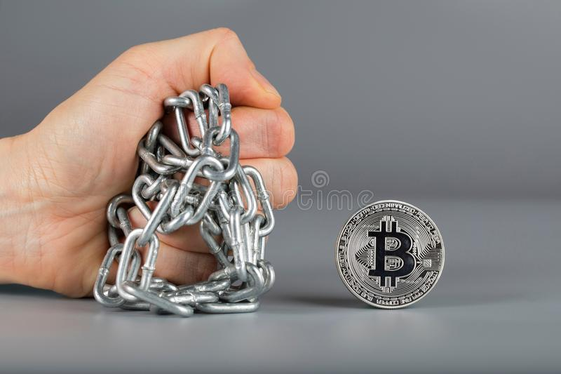 Human fist and bitcoin. Closeup royalty free stock images