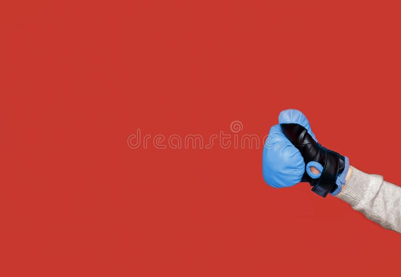 Human fist with a blue boxing glove. Throwing a punch isolated on the red background. Copy space on the left side royalty free stock photo