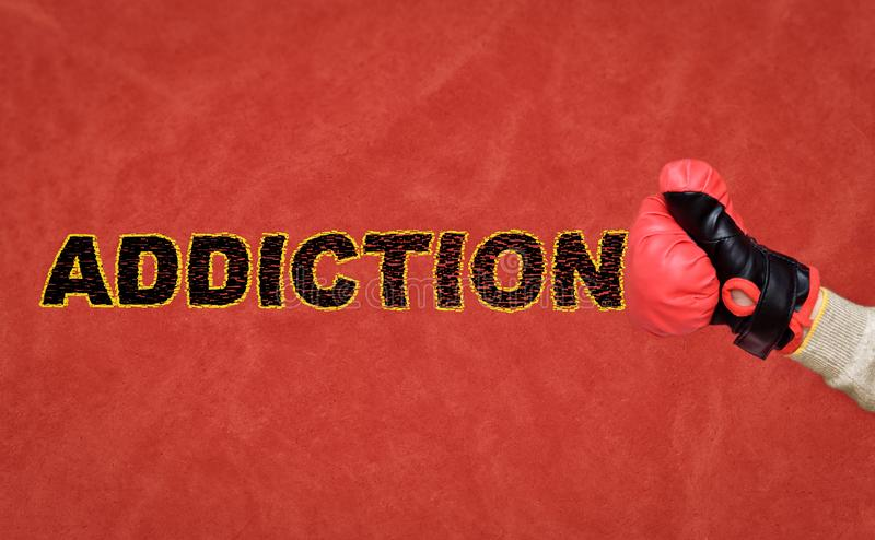 Human fist with a boxing glove hitting and breaking word addiction stock photos