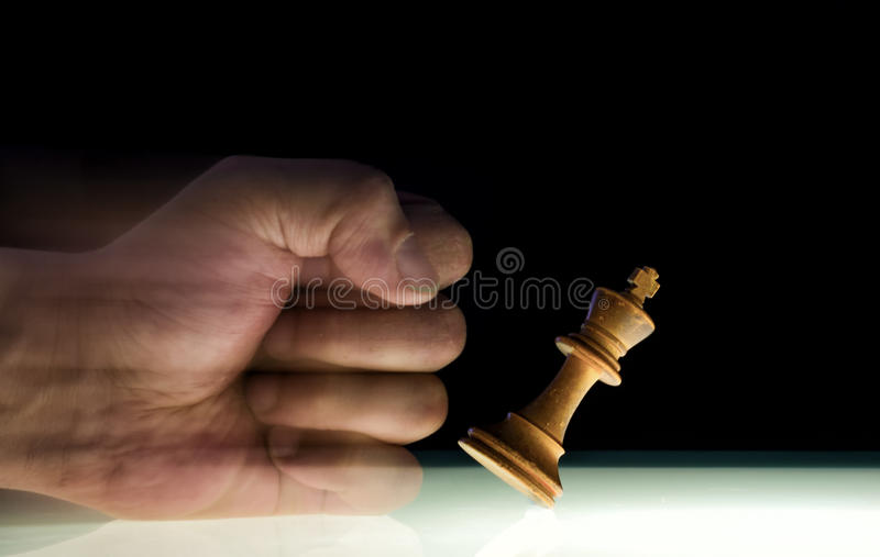 Human Fist Punches over a King Chess Piece stock photos