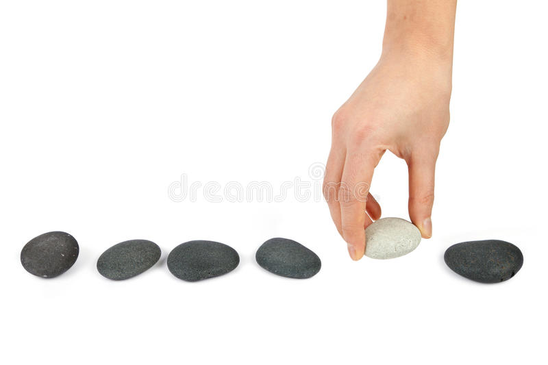 Human hand arranging line of pebbles stock images