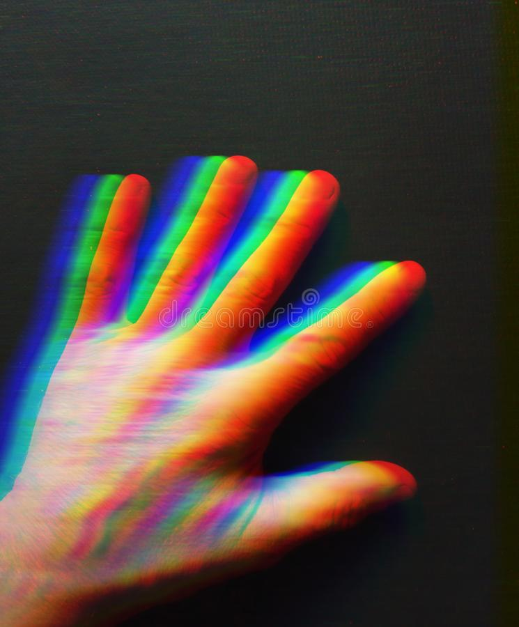 Human hand on a dark background. Rainbow colorful hand. On a dark background in motion. Man`s hand, abstract graphics. Fantasy form royalty free stock photo