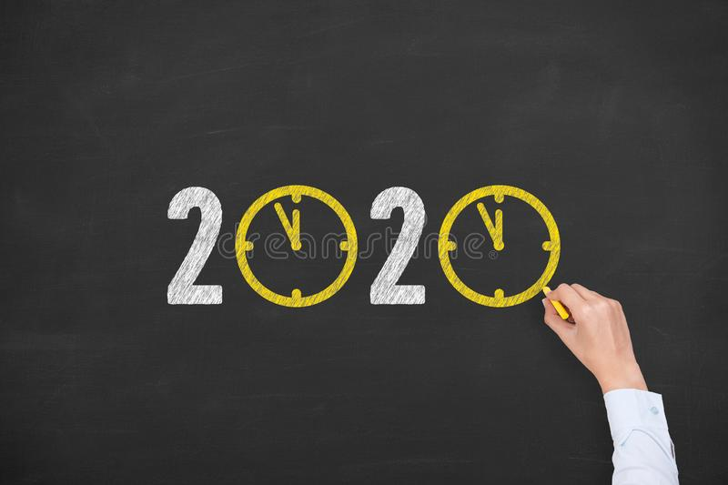 Human Hand Drawing New Year Concepts 2020 Countdown Clock on Blackboard Background royalty free stock image