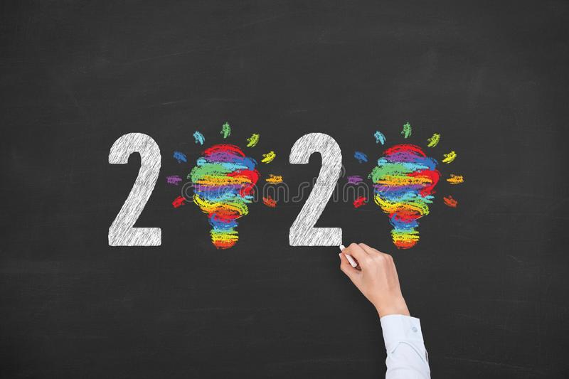 Human Hand Drawing New Year 2020 Creative Idea Concepts on Blackboard Background. New year concepts stock photos
