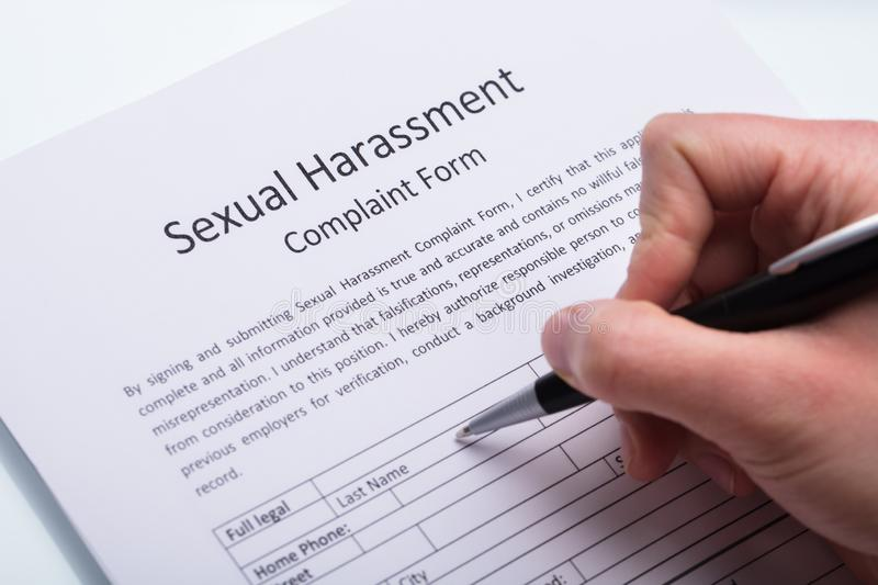 Human Hand Filling Sexual Harassment Complaint Form stock image