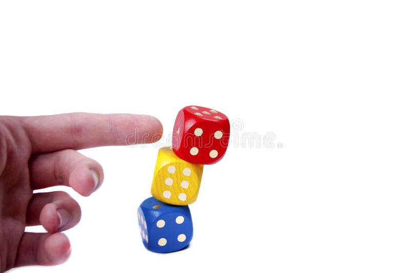 Human hand / finger pushing a tower like structure made of colorful game dices. Simple concept of no stability, demolition. Building falling over or stock photos