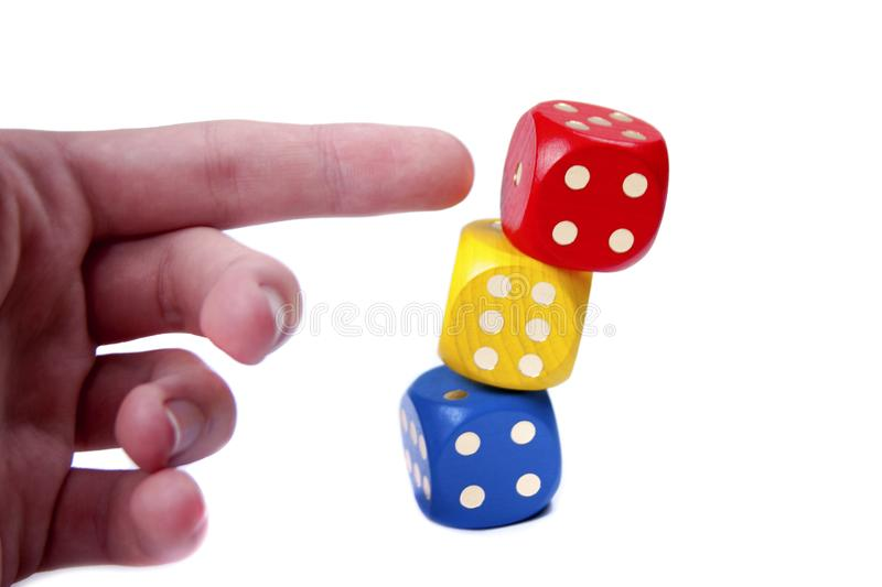 Human hand / finger pushing a tower like structure made of colorful game dices. Simple concept of no stability, demolition. Building falling over or royalty free stock photography